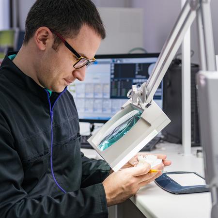 odontotecnico o dentista lavora con protesi dentali nel suo laboratorio Archivio Fotografico