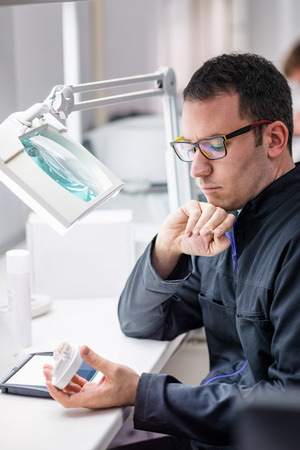 technologist: Dental technician or dentist working with tooth dentures in his laboratory