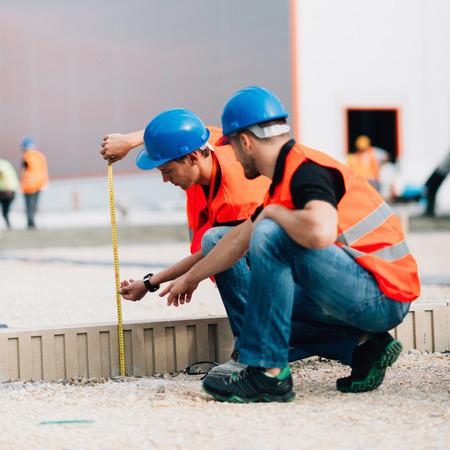 Bouwvakkers meten op de bouwplaats