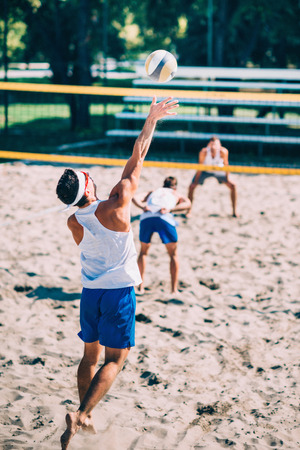 competitive: Male beach volleyball players in action