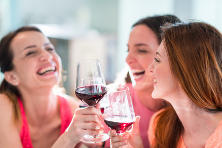 only three people: Friends drinking wine in restaurant Stock Photo