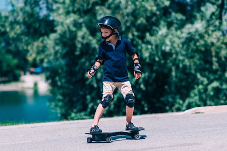 elbow pads: Little boy on the snakeboard by the lake