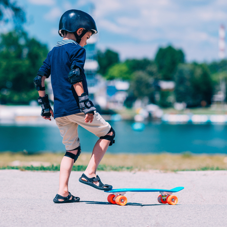 elbow pads: Little boy learning skateborading in park by the lake Stock Photo