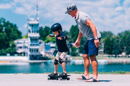 elbow pads: Grandfather and grandson trying a snakeboard Stock Photo
