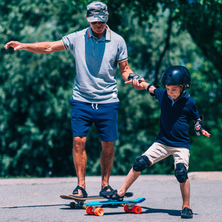 elbow pads: Grandfather and grandson skateboarding together Stock Photo