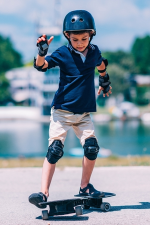 elbow pads: Little boy having fun with snakeboard Stock Photo