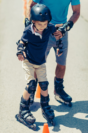 rollerskates: Senior teacher of roller skating with little boy practicing on class in the park Stock Photo