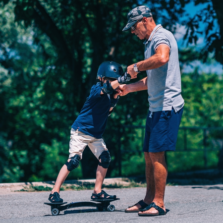 elbow pads: Little boy trying snakeboard with grandpa