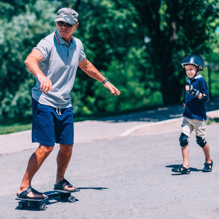 elbow pads: Grandfather and grandson snakeboarding Stock Photo