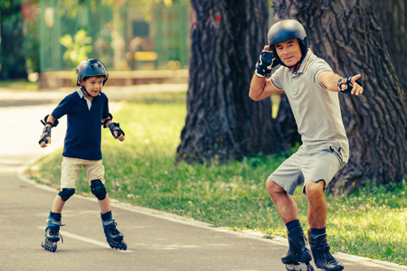 elbow pads: Grandfather teaching grandson roller skating in the park Stock Photo
