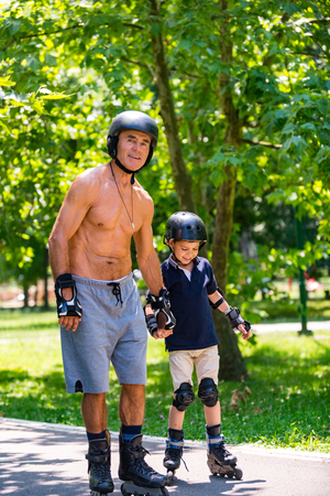 Grandfather teaching grandson roller skating in the park Stock Photo