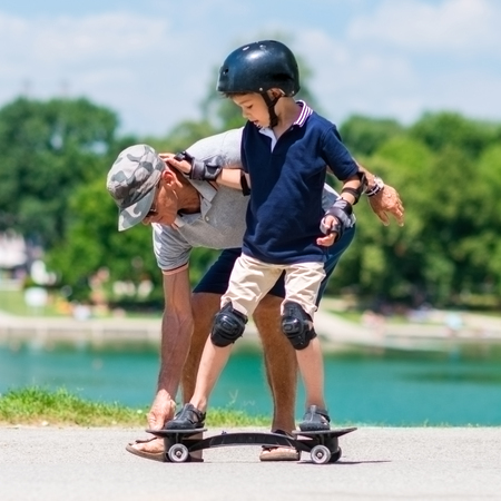 elbow pads: Little boy learning how to ride a snakeboard Stock Photo