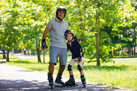 Grandfather and grandson roller skating in the park