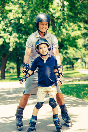 elbow pads: Grandfather and grandson roller skating in the park