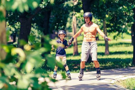 Little boy learning roller skating in park with his grandfather Stock Photo