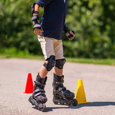 rollerskates: Boy practicing roller skating on class in the park