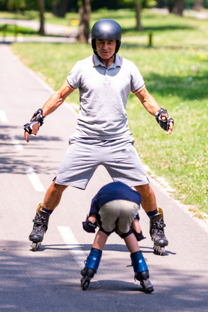 Roller skating in the park. Little boy with grandfather