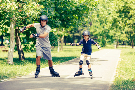 elbow pads: Grandfather and grandson having fun, roller skating in the park