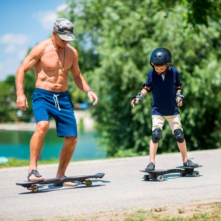 elbow pads: Senior man and little boy riding snakeboards