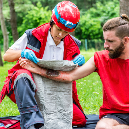 Medical worker treating burns on males hand. First aid treatment outdoors. First aid practice