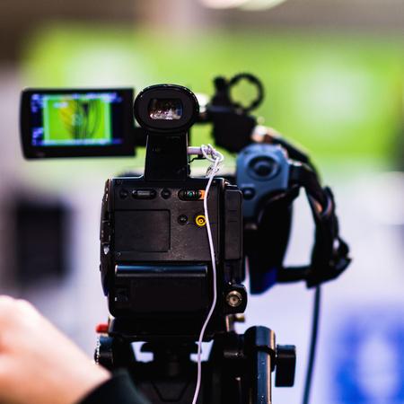 Video camera recording press conference Stock Photo