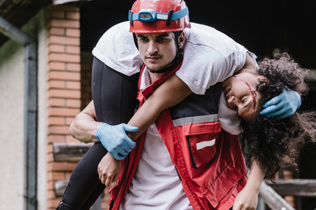 Rescue worker carrying disater victim Standard-Bild