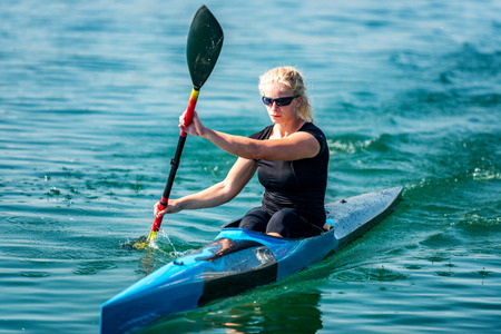 Female athelete training kayaking on lake