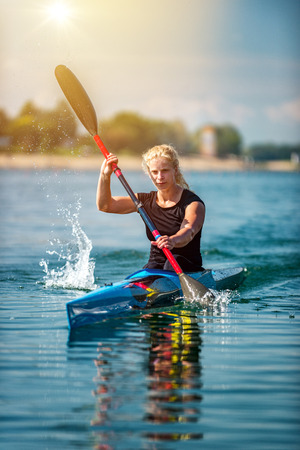 Female athelete training kayaking on lake