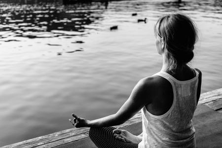 buena postura: Mujer en positin de loto practicar yoga en el lago.