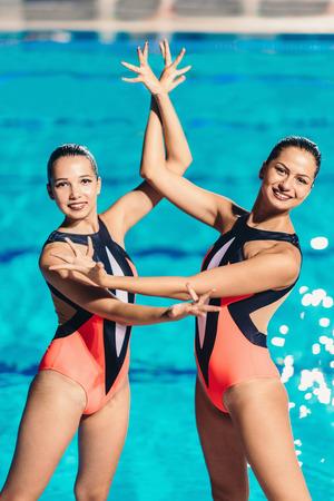 Synchroonzwemmen duet op de prestaties bij het zwembad