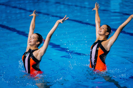 natación sincronizada: Synchronized swimming duet on performance  in the pool