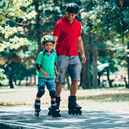 Father and son roller skating Stock Photo