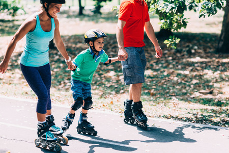 Cheerful family roller skating in park Stock Photo