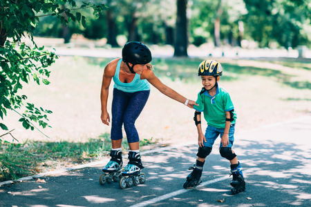 teching: Mother teching son roller skating in park Stock Photo