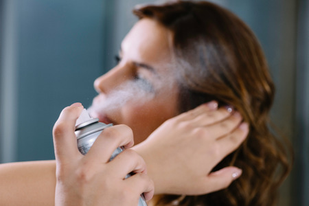 Pulvérisation cheveux avec de la laque dans un salon de coiffure Banque d'images - 66325868