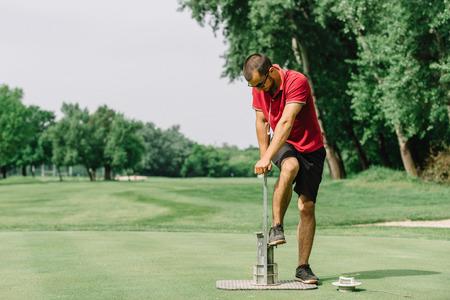 Golf course maintenance, greenskeeper cutting a golf hole