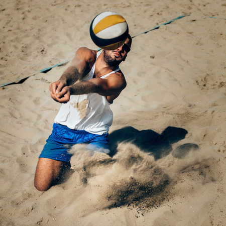 Male beach volleyball player in action hitting ball
