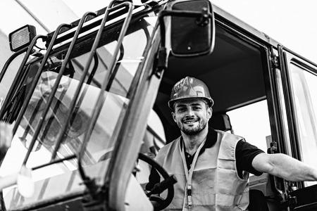 skid: Construction worker operating on Skid Steer Loader