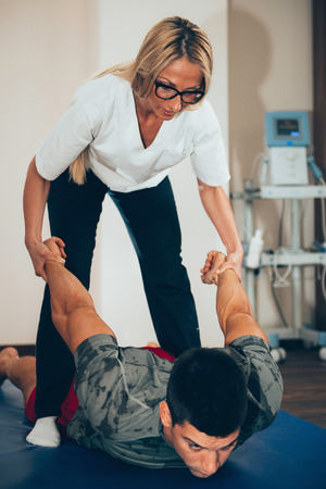Male exercising with Physical therapist