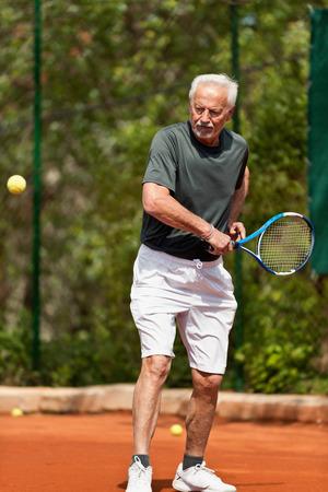 70s tennis: Senior man on tennis court