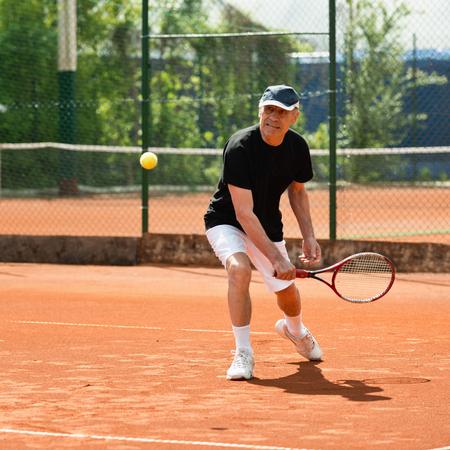 年配の男性のテニスコートでボールを打つ