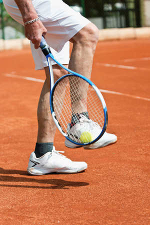 70s tennis: Taking ball with racquet from tennis court