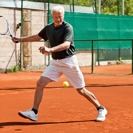 70s tennis: Active senior man playing tennis