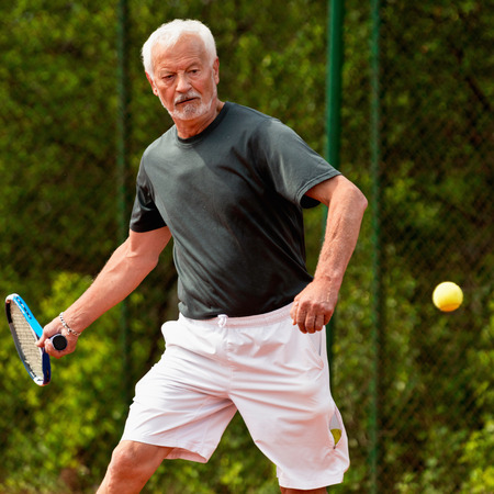 70s tennis: Senior tennis player playing tennis Stock Photo