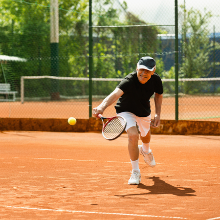 70s tennis: Senior male on tennis court