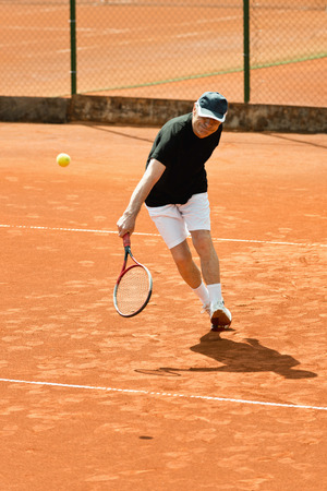 70s tennis: Senior male player hitting ball