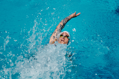 backstroke: Female with tattoos swimming backstroke on training