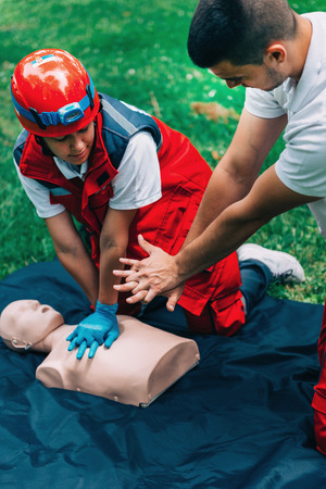 Cpr practice of woman and man on cpr dummy outdoors