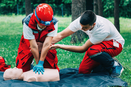 chest compression: Cpr practice of woman and man on cpr dummy outdoors