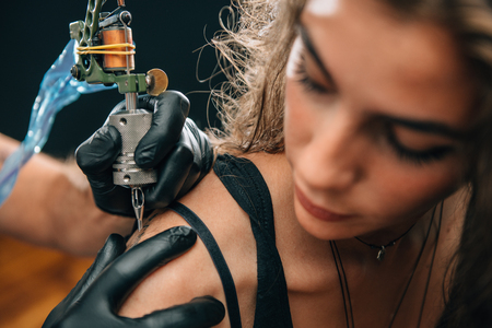 Tattooing. Pretty girl getting a shoulder tattoo. Focus on tattoo machine. Toned image 版權商用圖片